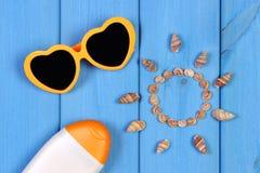 Seashells в форме солнца, солнечных очков и лосьона солнца на голубых досках, аксессуарах на лето Стоковое Изображение RF