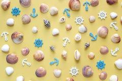 Seashells, декоративные анкеры и картина рулевых колес на желтой предпосылке Стоковое Фото