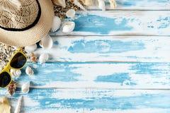 Seashells на голубой деревянной доске с соломенной шляпой и солнечными очками Стоковые Изображения