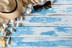 Seashells на голубой деревянной доске с соломенной шляпой и солнечными очками Стоковая Фотография RF
