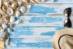 Seashells на голубой деревянной доске с соломенной шляпой и солнечными очками Стоковое Фото