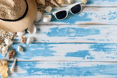 Seashells на голубой деревянной доске с соломенной шляпой и солнечными очками Стоковые Фото