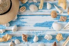 Seashells на голубой деревянной доске с соломенной шляпой Стоковые Фотографии RF