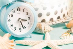 Seashells, alarm clock and beach accessories on a blue table - summer vacation and vacation time concept.  royalty free stock images