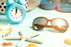 Seashells, alarm clock and beach accessories on a blue table - summer vacation and vacation time concept.  stock images