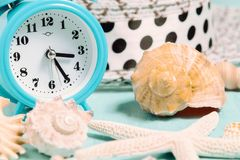 Seashells, alarm clock and beach accessories on a blue table - summer vacation and vacation time concept.  royalty free stock photos