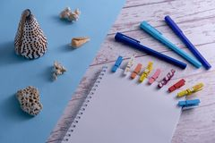 Seashells on a blue background, white paper sheets with colorful pegs and pens on a wooden table. Concept of summer travel stock photography