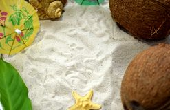 Seashells, coconuts and cocktail umbrellas are framing copy space on a beach sand. Summer holiday concept Royalty Free Stock Images