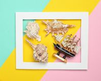 Seashells and decorative wooden ship in a white rectangular frame on a colored pastel background. Minimalist trend, top view. Seashells and decorative wooden Royalty Free Stock Photo