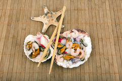 Seashells filled with fresh seafood and sticks Royalty Free Stock Photos