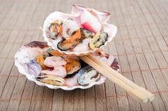 Seashells, fresh seafood and sticks Royalty Free Stock Photography