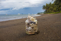 Seashells in glass on the sand beach. Cloudy sky evening. Tropical landscape with sea, white boats, coco palm trees Stock Photo