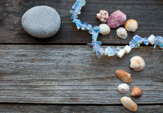 Seashells and pebbles on the wooden table Royalty Free Stock Photos