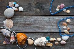 Seashells and pebbles on the wooden table Stock Images
