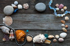 Seashells and pebbles on the wooden table Royalty Free Stock Photo
