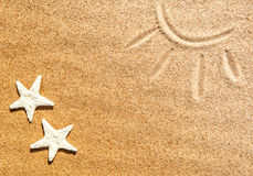 Seashells and picture of sun on the sand Royalty Free Stock Image