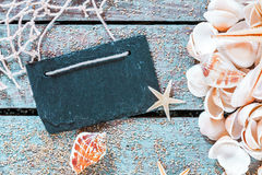 Seashells with a retro school slate on rustic wood Royalty Free Stock Photography