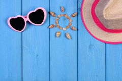 Seashells in shape of sun, sunglasses and straw hat on blue boards, accessories for summer, copy space for text Royalty Free Stock Photos