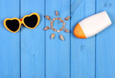 Seashells in shape of sun, sunglasses and sun lotion on blue boards, accessories for summer, copy space for text Royalty Free Stock Photography