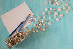 Seashells spill out of the bottle glass, sheets of paper  and pen on a blue background. Stock Photo