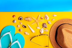 Seashells and stars. Straw hat and mint slippers on yellow and blue background stock photography