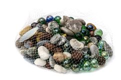 Seashells and stones in net bag on white background royalty free stock photography
