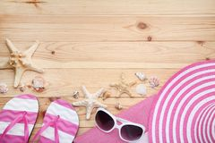 Seashells with sunglasses and flip flops. Different seashells with sunglasses and flip flops on wooden table royalty free stock image