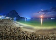 Красивый ландшафт ночи на seashore с желтым песком, полнолунием, горами и лунным путем moonrise Каникулы на пляже Стоковое фото RF