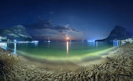 Красивый ландшафт ночи на seashore с желтым песком, полнолунием, горами и лунным путем moonrise Каникулы на пляже Стоковое Изображение RF