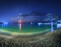 Красивый ландшафт ночи на seashore с желтым песком, полнолунием, горами и лунным путем moonrise Каникулы на пляже Стоковая Фотография RF