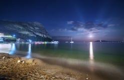 Красивый ландшафт ночи на seashore с желтым песком, полнолунием, горами и лунным путем moonrise Каникулы на пляже Стоковые Изображения RF