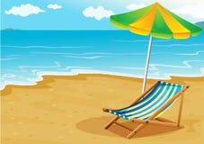 A seashore with a bench and an umbrella Stock Photo