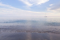 Seashore and boat. Small sailboat on a calm sea seen from seashore during early evening. The picture was taken in Spain Royalty Free Stock Photos