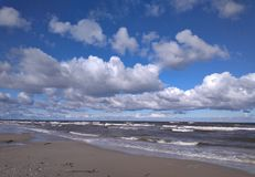 Seashore with clouds during stormy weather. Baltic seashore on Polish coast with beach and waves during windy weather Stock Photography
