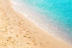 Seashore with footprints on the sand, light blue sea Royalty Free Stock Photo