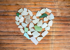 Seashore glass pebble heart on wooden background. Sugar glass mosaic for Valentine`s Day. Stock Images
