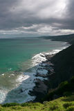 Seashore and green ocean under dark clouds. Reef on seacaost , green ocean, white waves, grand ocean road, south australia Stock Photos