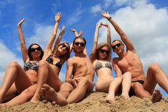 Seashore holidays. Cheerful young people having fun on a beach. Great summer holidays Stock Images