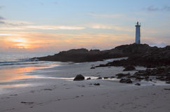 Seashore with Lighthouse. A lighthouse on the rocks of the seashore at the sunset time Royalty Free Stock Photo