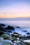 Seashore with misty water at sunset Stock Photography