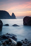 Seashore with misty water at sunset Stock Image