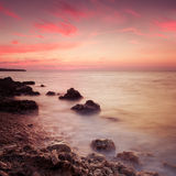 Seashore with misty water at sunset Stock Photos