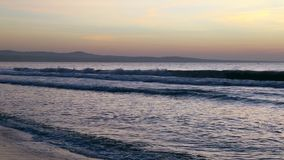 Seashore panning right sandy beach. Golden sunset ocean horizon. Sea waves blue water and orange sunlight. Beautiful landscape calm scenery. Serene tropical stock video