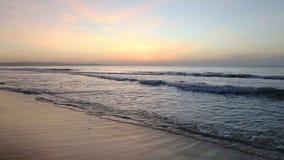 Seashore panning sandy beach. Golden sunset ocean horizon. Sea waves blue water and orange sunlight. Beautiful landscape calm scenery. Serene tropical panorama stock footage