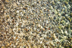 Seashore pebble over water Stock Photo