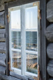 Seashore reflection in rustic cottage window of old wooden pisca. Torial house Royalty Free Stock Photos