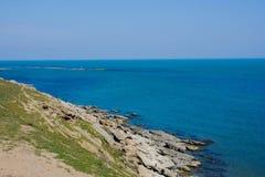 Seashore, rocks, blue water, Caspian sea. Seashore, rocks, blue water royalty free stock photography