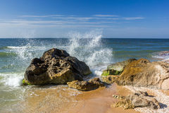 Seashore with rocks and splashing waves. With spray Royalty Free Stock Photo