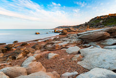 Rocks on seashore. Seashore, rocks and surf on beach Stock Images