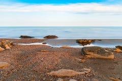 Seashore, sky, blue water. Seashore, rocks and surf on beach Royalty Free Stock Photo